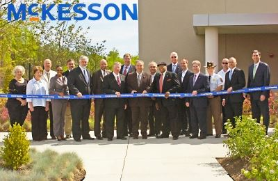 A group of men and women at a ribbon cutting